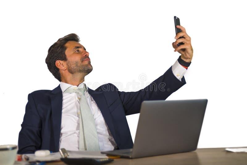 在运作在公司公司办公计算机书桌的衣服的年轻可爱和确信的商人采取selfie画象pictur 库存图片