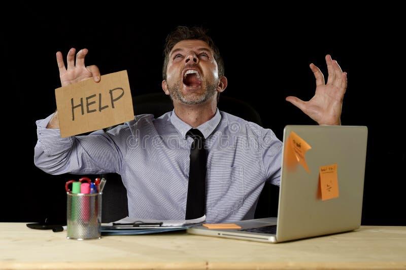 在运作在办公计算机书桌的重音的商人拿着标志请求帮助尖叫疯狂 库存图片