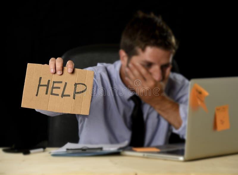 在运作在办公计算机书桌的重音的疲乏的绝望商人拿着标志请求帮忙 免版税库存照片