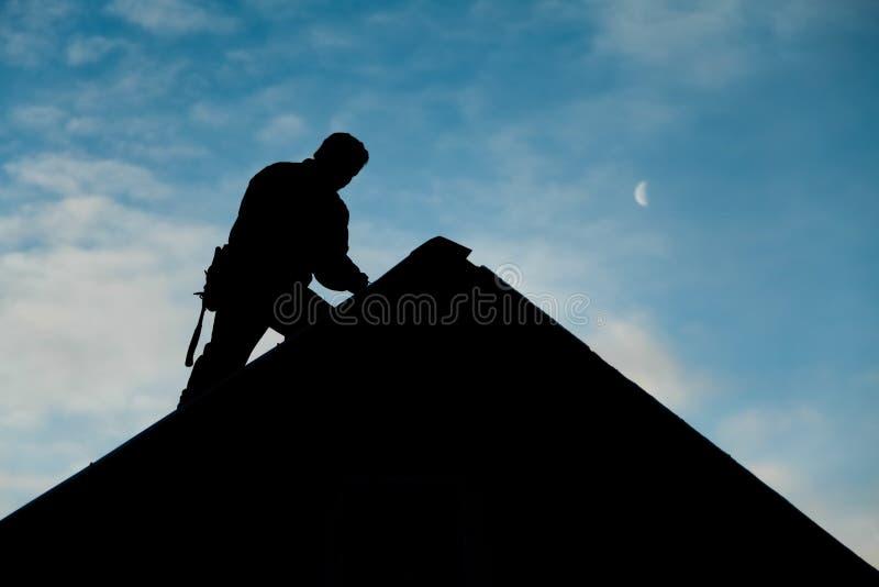 在运作在屋顶上面的剪影的承包商 免版税库存图片