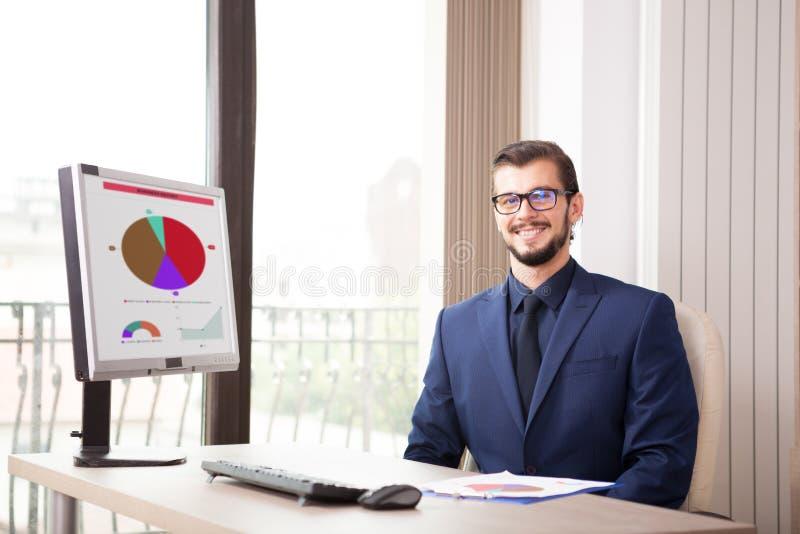 在运作在他的计算机的衣服的商人在玻璃风旁边 图库摄影