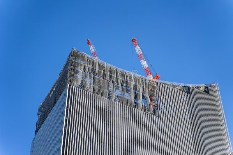 在运作的塔顶部的建筑用起重机在发展城市修建高skycrapper办公楼,清楚的天空蔚蓝 图库摄影