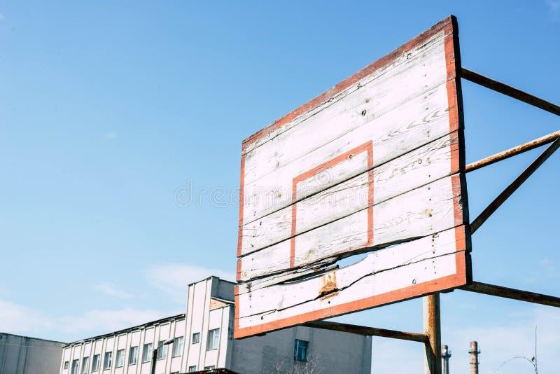 在运动场的老篮球圆环 库存图片