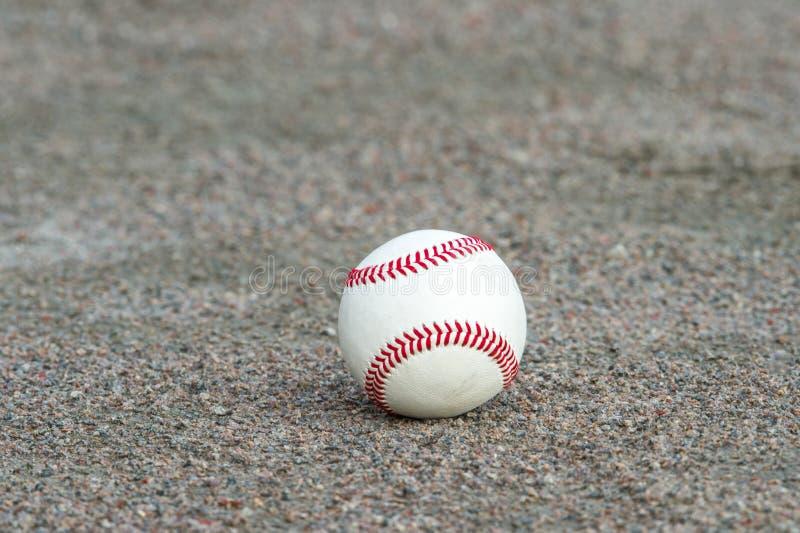 在运动场耕地的一棒球  免版税库存照片