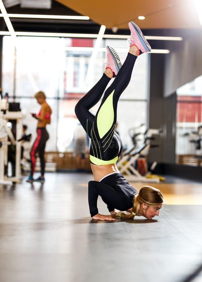 在运动服打扮的年轻运动女孩做在地板上的手倒立在现代健身房 库存图片