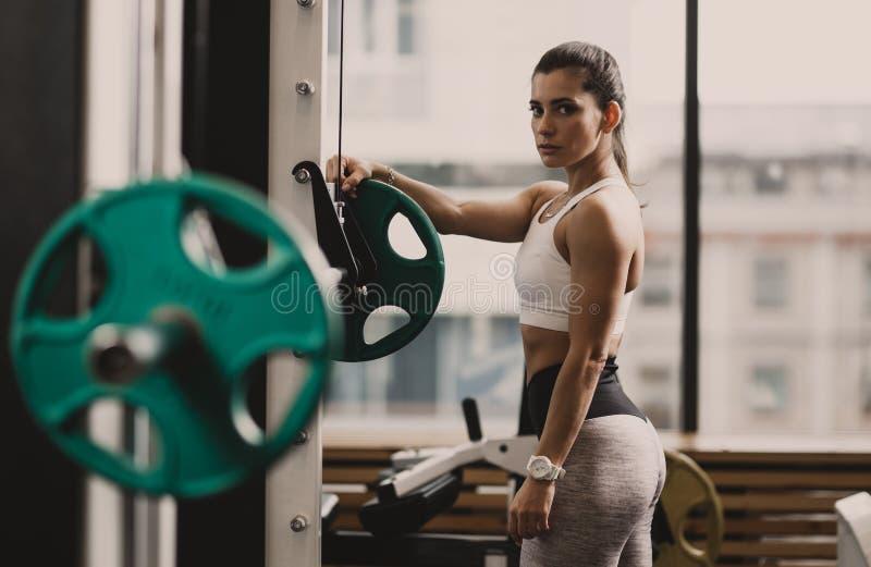 在运动服打扮的运动女孩准备杠铃练习在现代健身房的举重 图库摄影