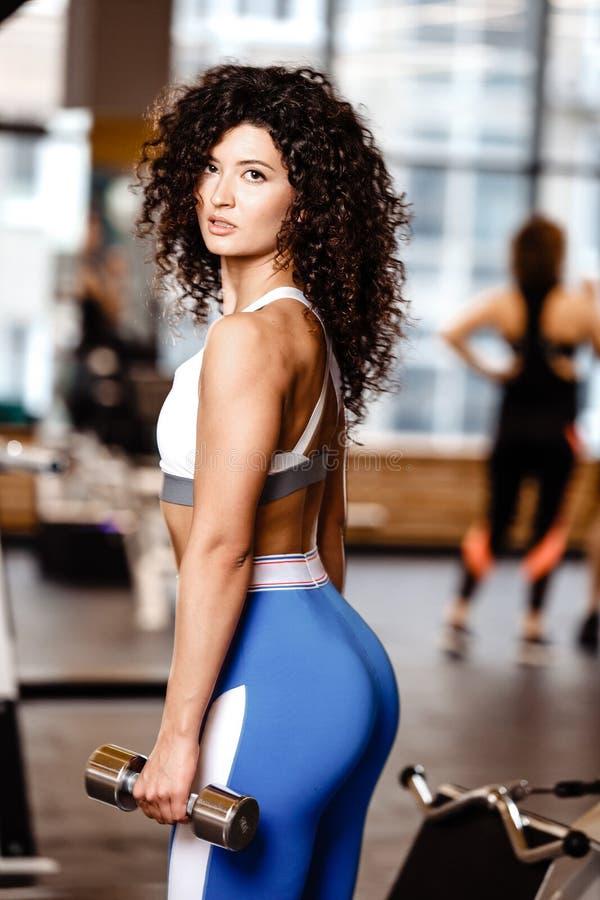 在运动服打扮的Atletic黑暗头发卷曲女孩在她的手上站立与哑铃在现代健身房 库存照片