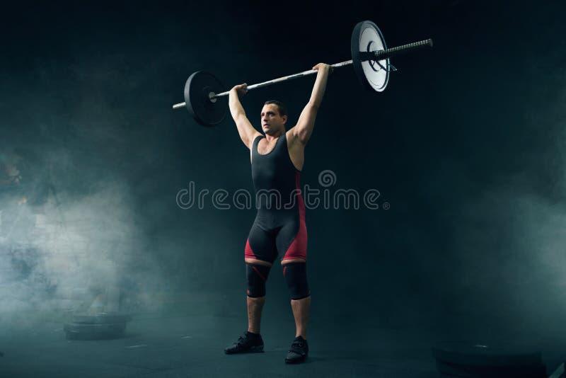 在运动服的强的举重者采取重量 免版税库存图片