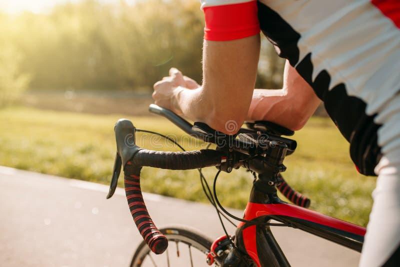 在运动服的男性bycyclist,循环在自行车道路 免版税库存图片