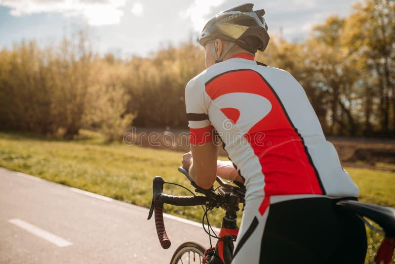 在运动服的男性bycyclist,循环在自行车道路 库存图片