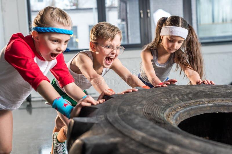 在运动服训练的可爱的孩子与在健身演播室的轮胎 库存图片