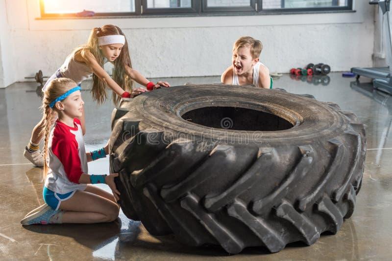 在运动服训练的可爱的孩子与在健身演播室的轮胎 免版税库存照片