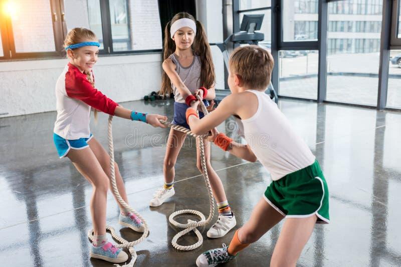 在运动服训练的可爱的孩子与在健身演播室的绳索 免版税库存照片