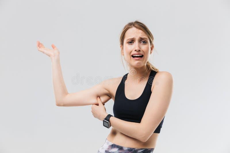 在运动服20s的打扮的图象失望的白肤金发的妇女哭泣,当接触她的在锻炼期间的肥胖胳膊在健身房是时 免版税库存照片