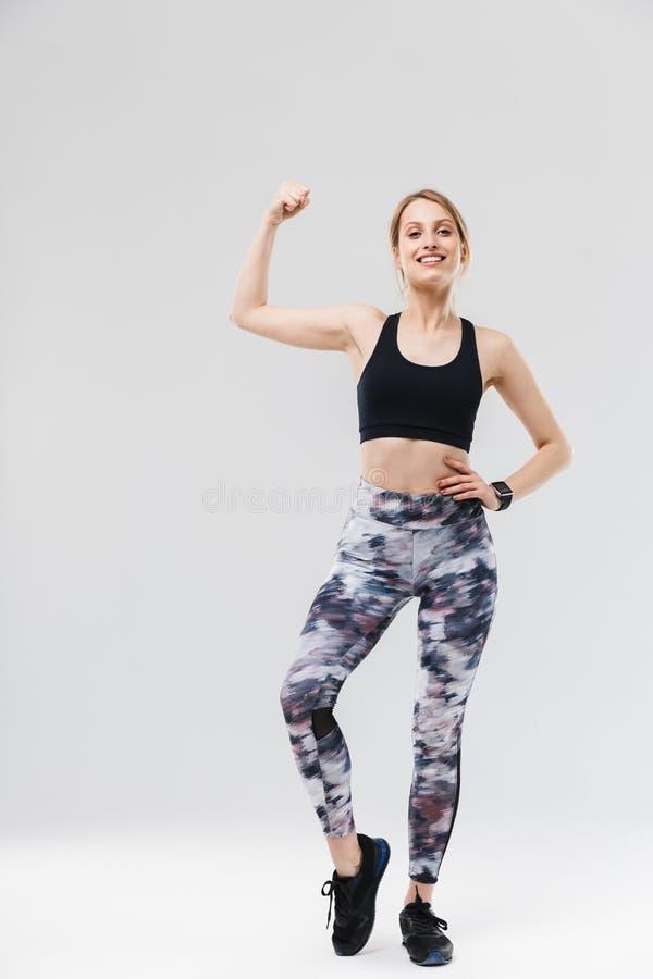 在运动服20s的打扮的全长图象适合的白肤金发的妇女微笑和显示二头肌,当做锻炼在健身房时 免版税库存图片