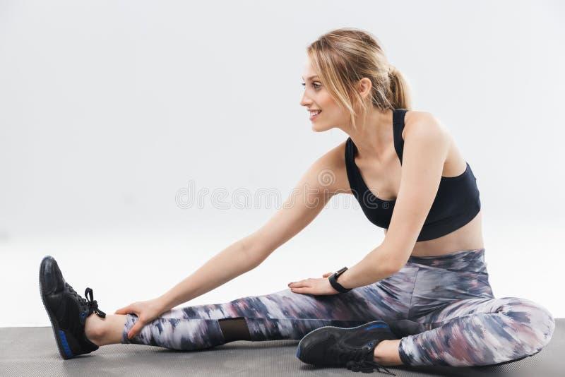 在运动服20s的打扮的图象快乐的白肤金发的妇女制定出和舒展她的身体在有氧运动期间 库存图片