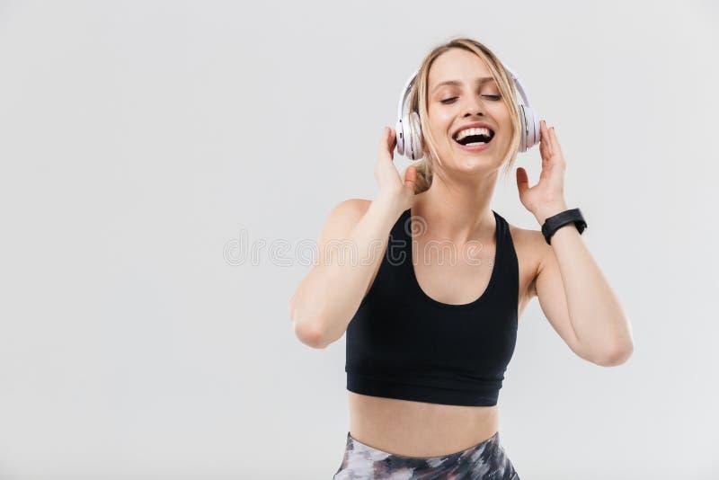在运动服20s的打扮的图象快乐的白肤金发的妇女听到与耳机的音乐在健身房的锻炼期间 库存照片