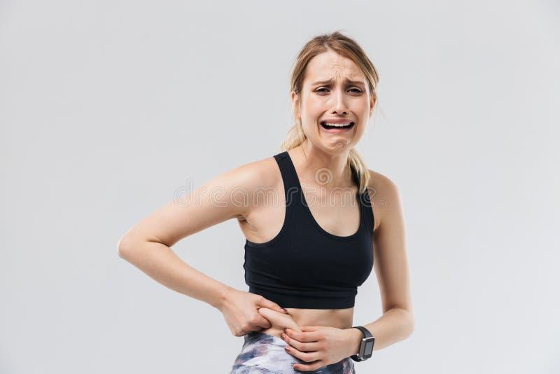 在运动服20s的打扮的图象生气白肤金发的妇女哭泣,当接触她的肥胖腹部在健身房时的锻炼期间 免版税图库摄影