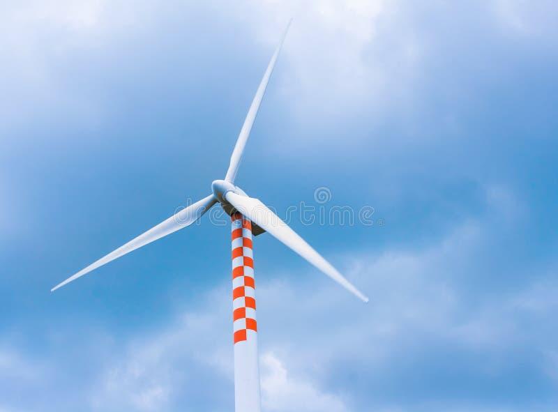 在运动的风轮机在蓝天和云彩下 免版税图库摄影