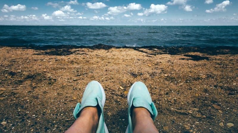 在运动鞋基于的女性腿沿海概念的海滩 库存图片
