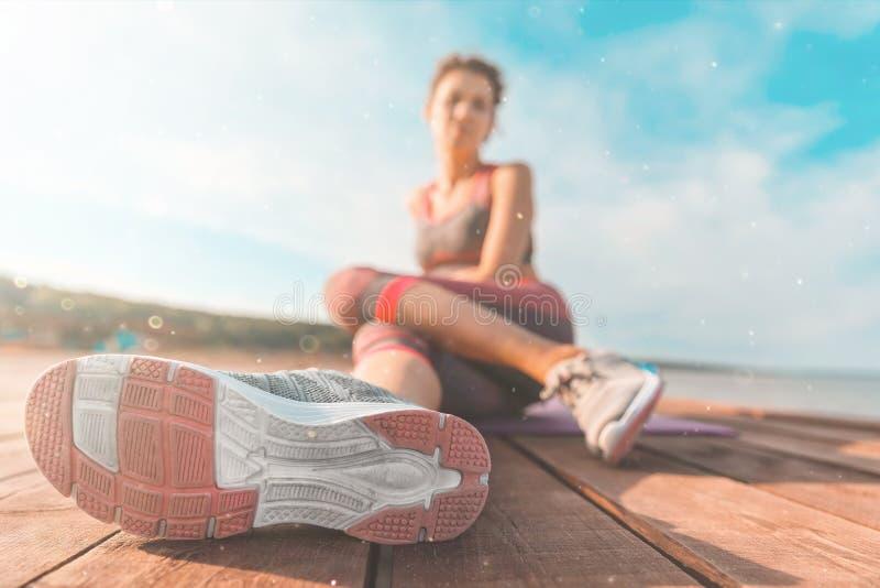 在运动鞋特写镜头的腿 健康和瑜伽概念 强的运动女性腿和跑鞋的背面图关闭  免版税库存照片