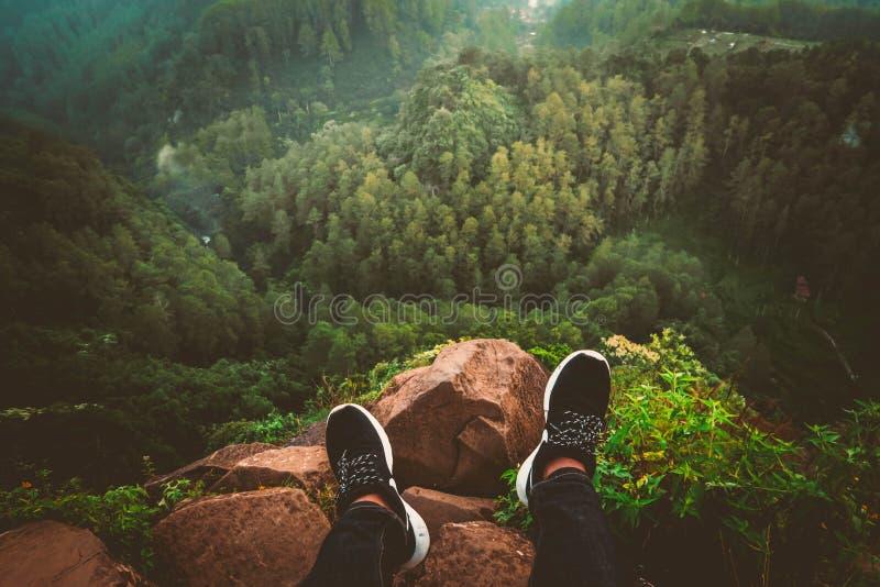 在运动鞋的人的脚坐看一个美丽的森林和小山的一个岩石峭壁边缘 免版税库存图片