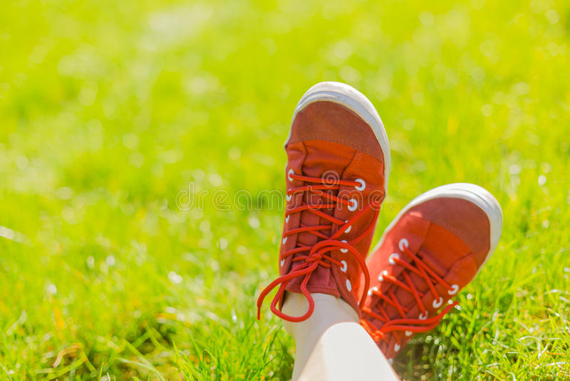 在运动鞋的脚在绿草 图库摄影