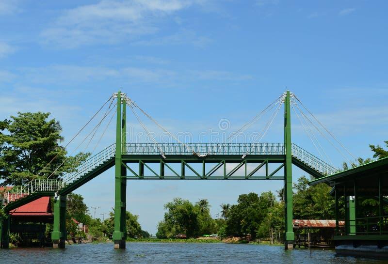 在运河和蓝天的绿色吊索铁桥梁 库存照片