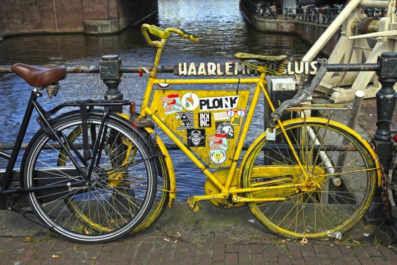 在运河桥梁,阿姆斯特丹的葡萄酒黄色自行车 免版税库存照片