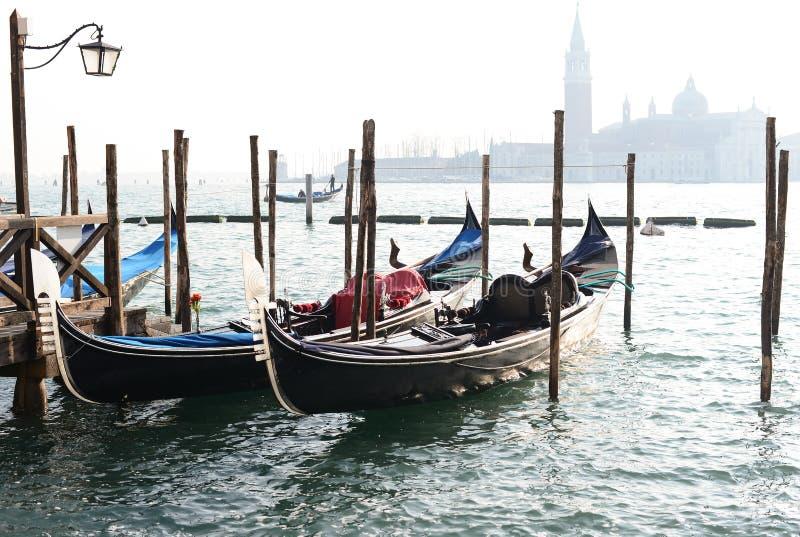 在运河的传统长平底船重创与圣乔治Maggiore教会 免版税图库摄影