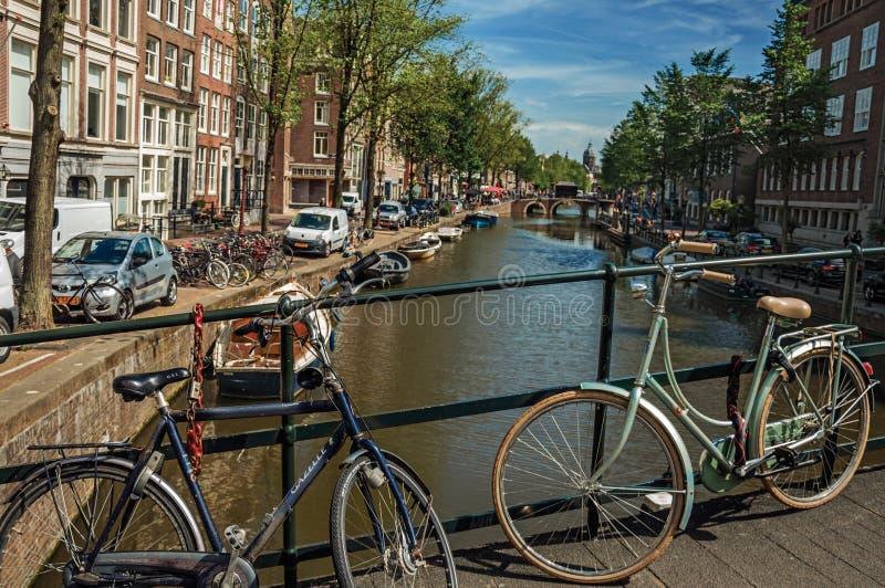 在运河的桥梁有自行车的黏附了在楼梯栏杆并且停泊了小船在阿姆斯特丹 免版税库存图片