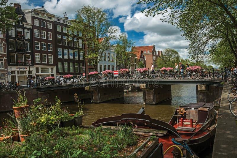 在运河的桥梁有被停泊的小船、通过在阿姆斯特丹的人民和骑自行车者的 库存照片