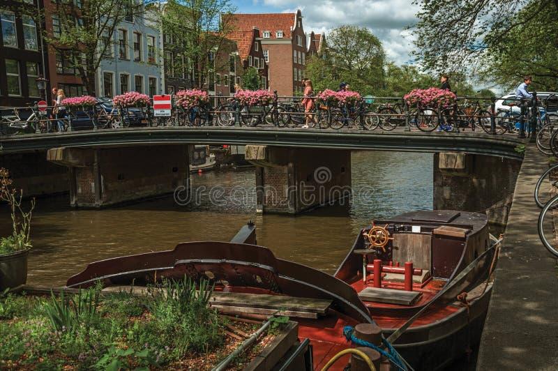 在运河的桥梁有被停泊的小船、通过在阿姆斯特丹的人民和骑自行车者的 库存图片
