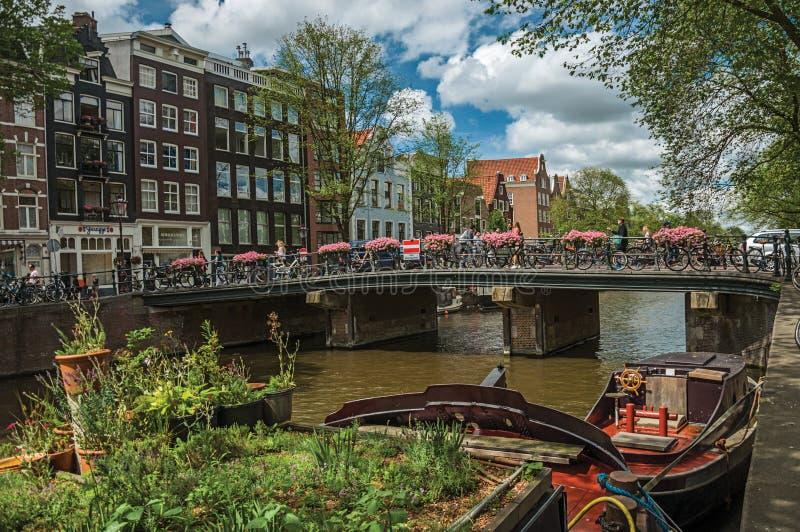 在运河的桥梁有被停泊的小船、通过在阿姆斯特丹的人民和骑自行车者的 免版税库存图片