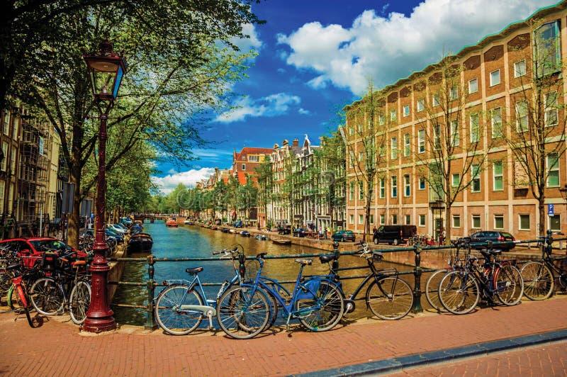 在运河的桥梁有铁楼梯栏杆、自行车、老大厦和小船的在阿姆斯特丹 库存照片