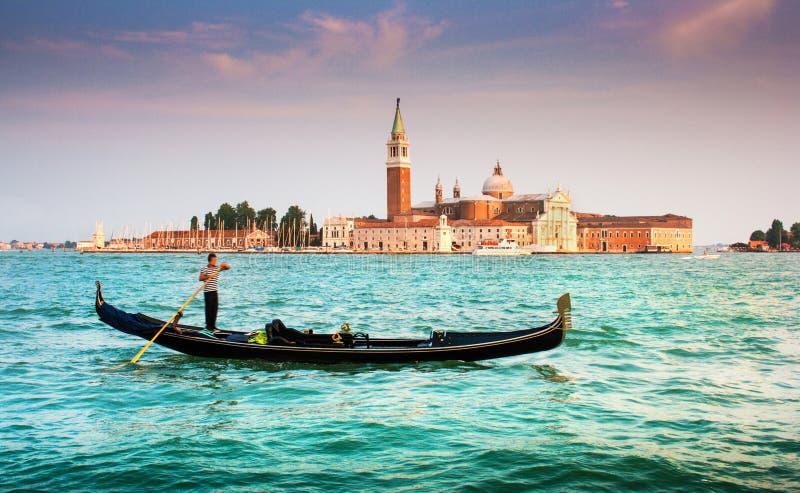 在运河的长平底船重创与圣乔治Maggiore在日落,威尼斯,意大利 库存照片