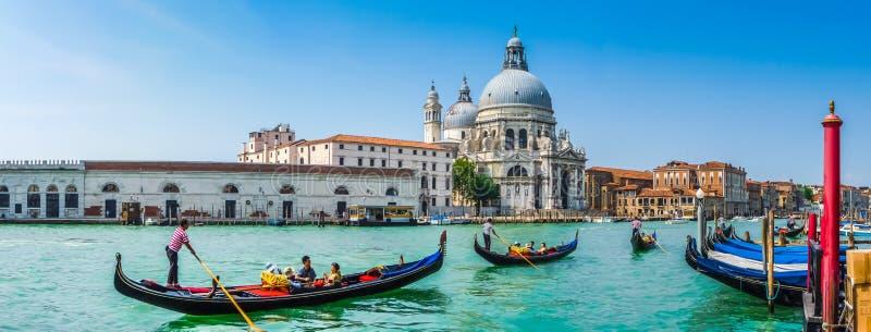 在运河的长平底船重创与大教堂二圣玛丽亚,威尼斯,意大利 免版税库存照片