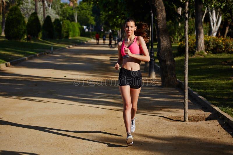 在运行在美好的棕榈背景的公园的明亮的运动服的有吸引力的母赛跑者 库存图片