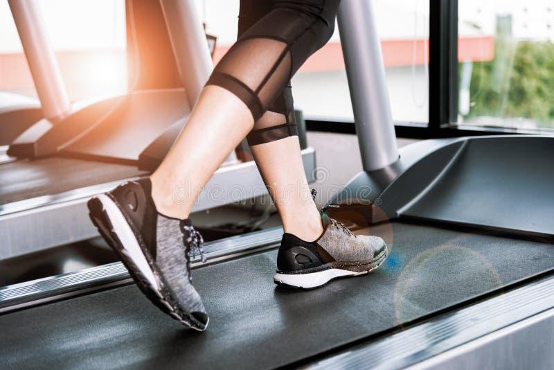 在运行在踏车的运动鞋的女性肌肉脚在健身房 库存图片