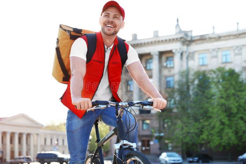 在运送食物的自行车的男性传讯者 库存图片