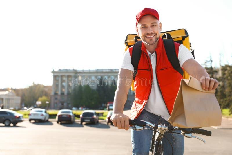 在运送食物的自行车的男性传讯者  图库摄影