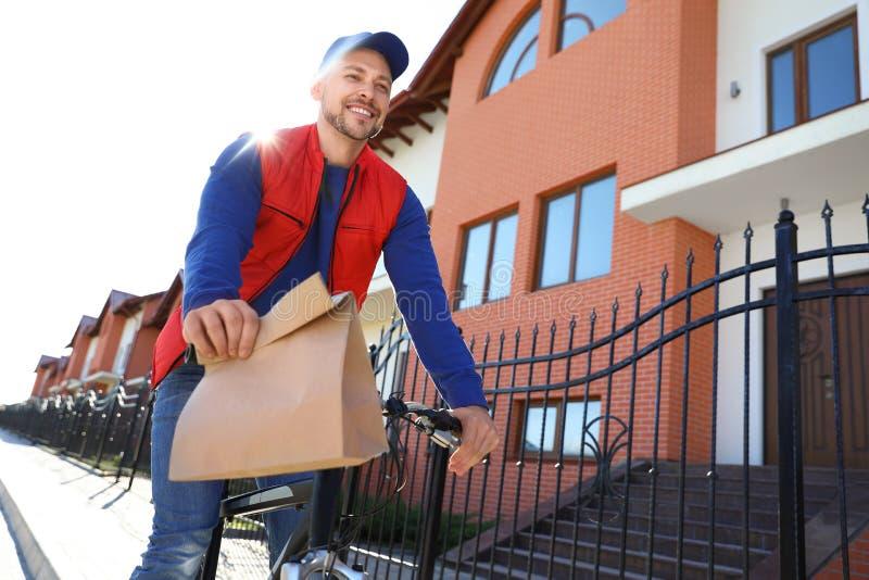 在运送食物的自行车的男性传讯者  库存照片