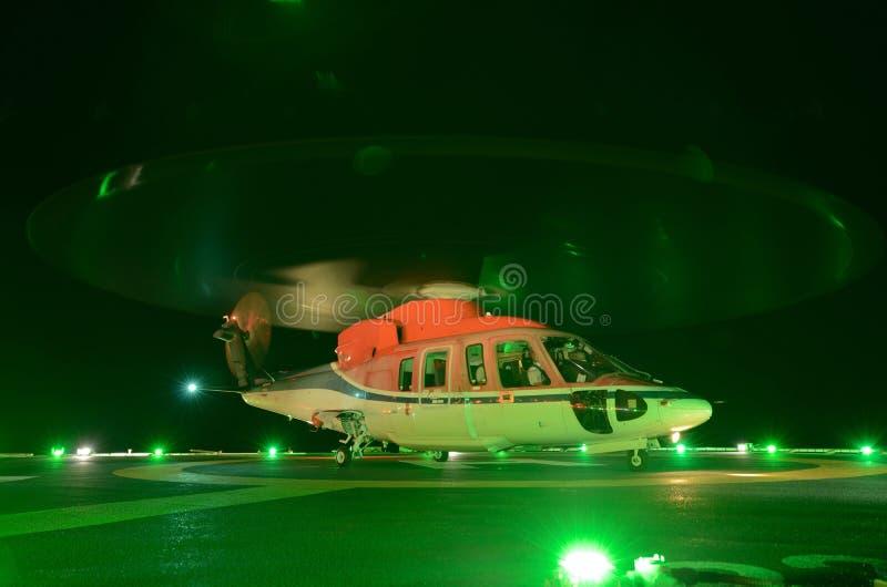 在近海抽油装置的直升机夜间着陆 库存图片