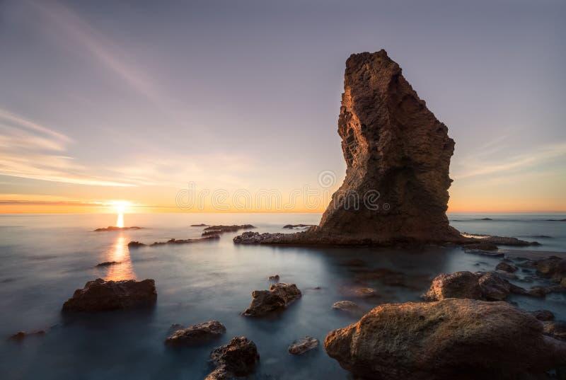 在这个海滩的黎明在卡沃内拉斯和莫哈卡尔,阿尔梅里雅西班牙省的两个镇之间,引人注意的岩石似乎 库存图片