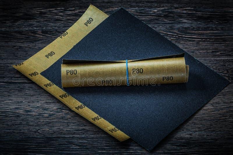 在这纸葡萄酒木头背景板料的滚动的沙纸  免版税库存图片