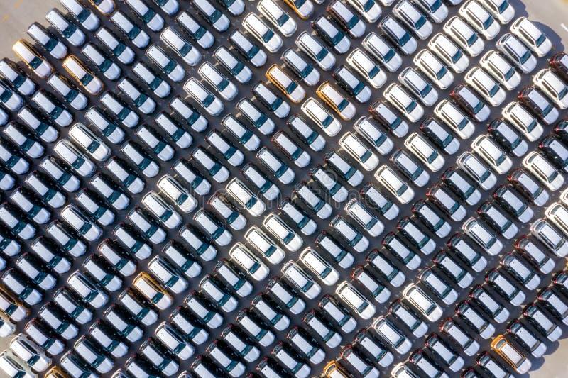 在进出口事务的口岸后勤和运输排队的空中顶视图新的汽车乘船在公海 ? 免版税库存图片