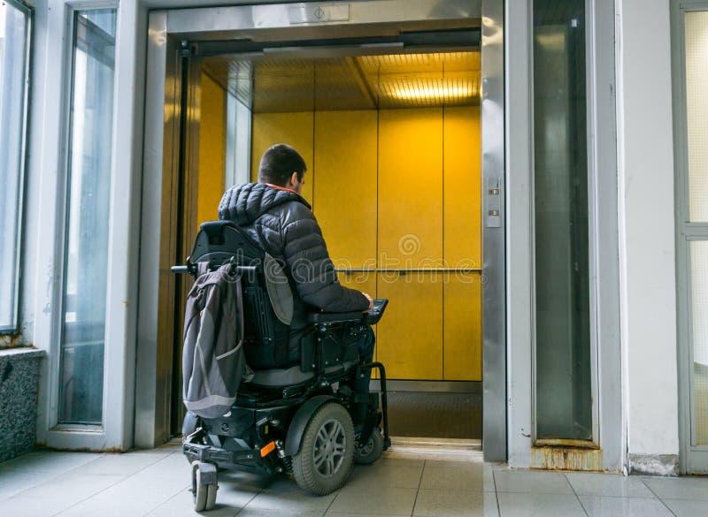 在进来在电梯的轮椅的有残障的男性 免版税库存图片