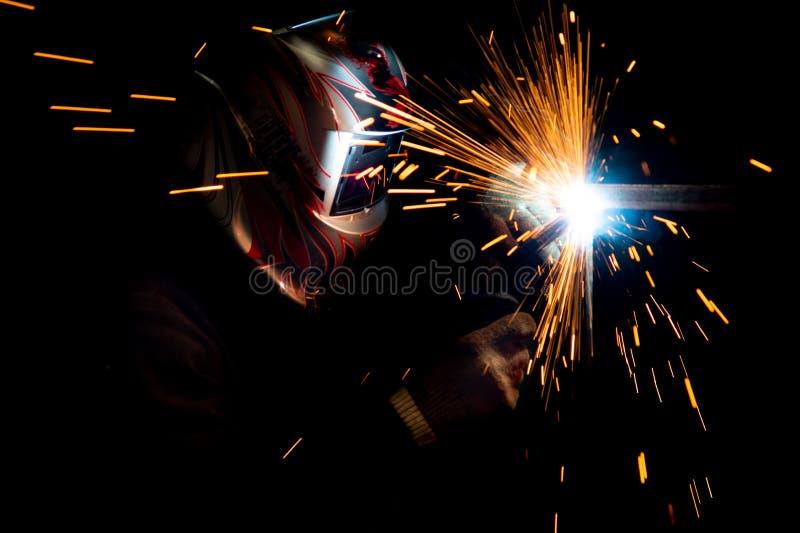 在进行金属焊接的面具的公焊工 在深色的照片 免版税库存照片