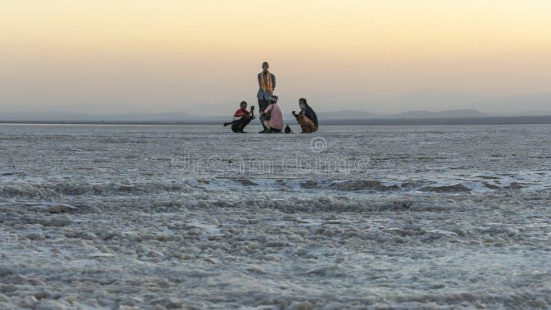 在远处祈祷在Asale湖盐平原的日落期间的战士Danakil消沉的在埃塞俄比亚,非洲 免版税库存图片