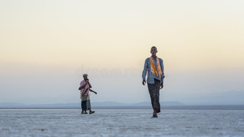 在远处走在Asale湖盐平原的日落期间的人Danakil消沉的在埃塞俄比亚,非洲 免版税库存照片